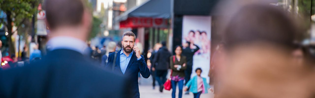 hipster-manager-with-smart-phone-walking-in-the-PFKTPR9(1)